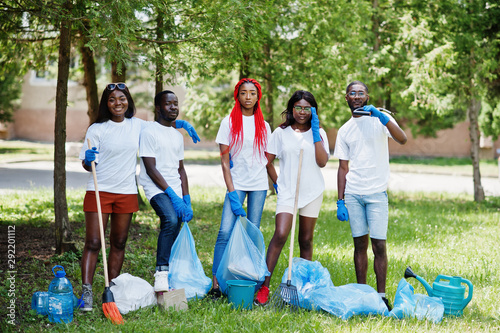 Group of happy african volunteers with garbage bags cleaning area in park Wallpaper Mural