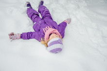 Little Girl Lying In Snow