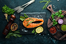 Grilled Salmon Steak On A Stone Plate. On An Old Background. Top View. Free Copy Space.