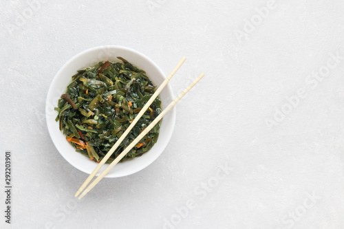 Seaweed salad with fermented algae on a white plate. Traditional Japanese food, asian cuisine. White background, top view, copy space