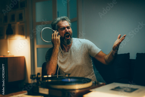 mid aged man playing records on gramophone and singing at his home. night scene - 292206977
