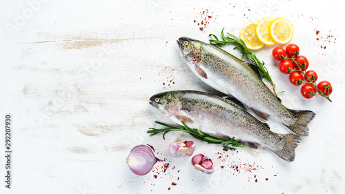 Fototapeta Raw fish with vegetables on a white wooden background. Fish trout. Top view. Free space for your text. obraz