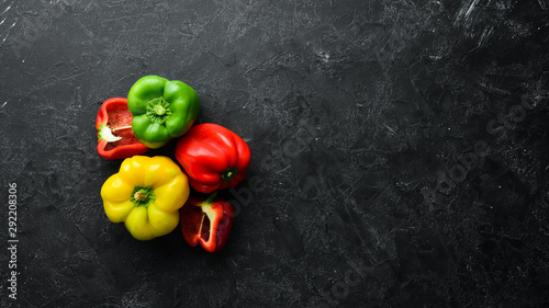 Fotografia Fresh colored paprika on black stone background