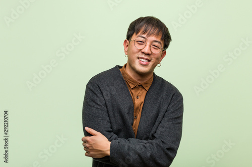 Fototapeta Young chinese man wearing a cool clothes style against a green background obraz