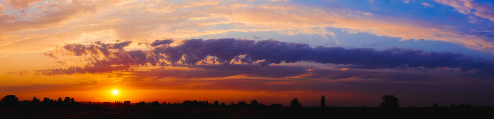 Bright sunlight through the clouds against a breathtaking evening sky at sunset. panorama, natural composition