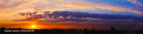Foto op Plexiglas Herfst Bright sunlight through the clouds against a breathtaking evening sky at sunset. panorama, natural composition