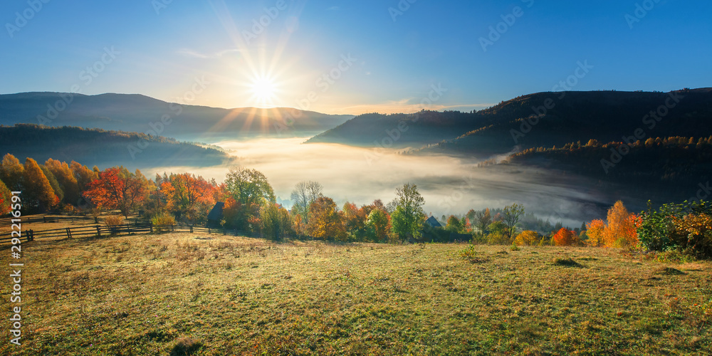 Fototapeta amazing countryside in fall season at sunrise. gorgeous view in to the valley full of fog in morning light. sun above the distant mountain. fence through rural field on the hillside. beautiful autumn
