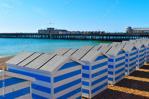 Foto auf AluDibond Cappuccino Hastings white and blue striped beach huts on a sunny morning await the holiday makers on the British coast. Sussex, South East England
