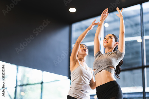 Foto op Canvas School de yoga Beautiful Asian woman learning yoga pose with female instructor in yoga studio or health club. Sport exercise activity, gymnastics or ballet dancing class, or healthy people lifestyle concept