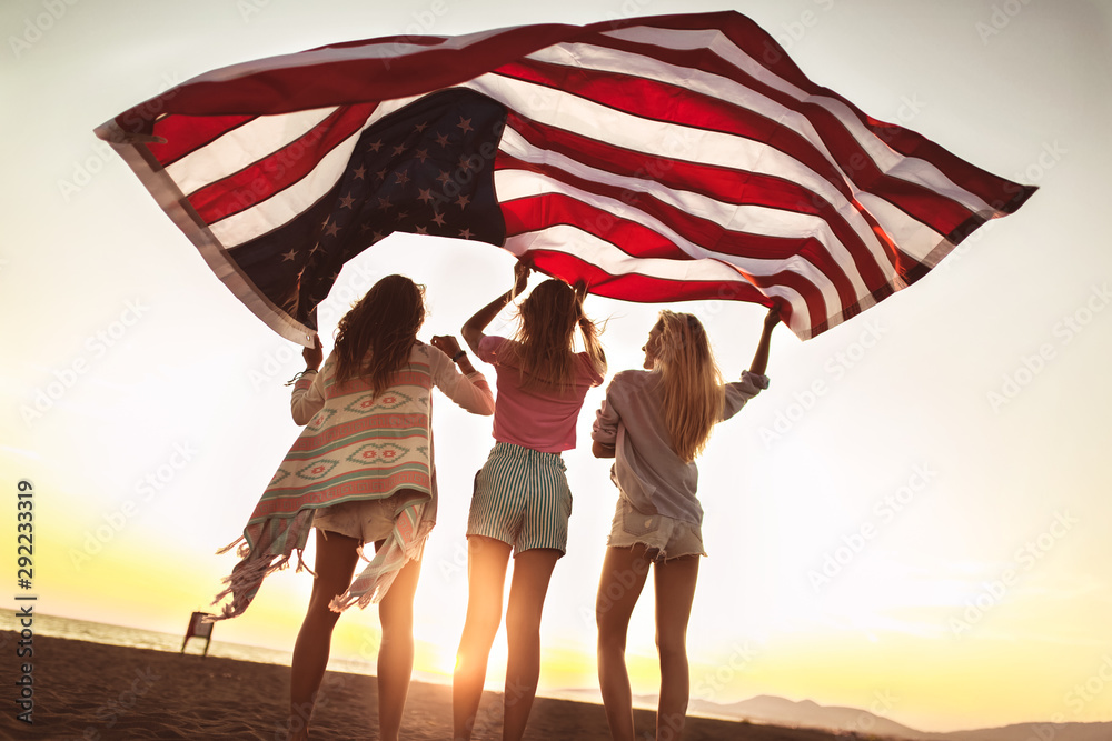 Fototapeta Young friends carrying american flag on the beach