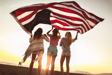 Young Friends Carrying American Flag On The Beach
