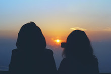 Silhouettes Of Two Women Looki...