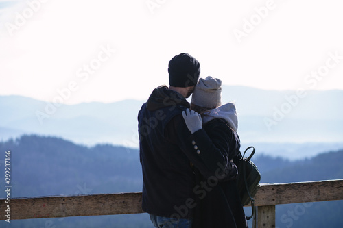 Silhouettes of young couple in love standing on the top of mountain Canvas Print