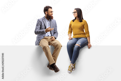 Obraz Bearded man talking to a young female seated on a banner - fototapety do salonu