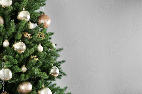 Foto auf Gartenposter Baume Beautiful Christmas tree with decor against light grey background. Space for text