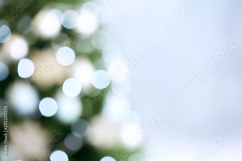 Fotografía  Beautiful Christmas tree with lights against grey background, blurred view
