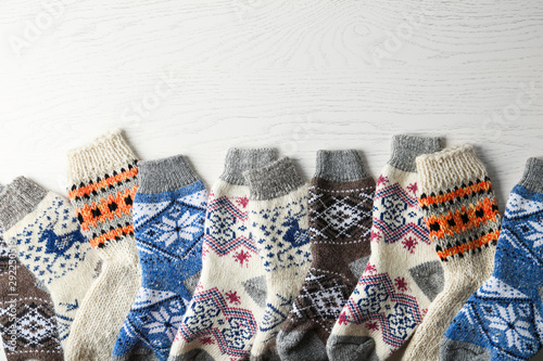 Poster Individuel Soft knitted socks on white wooden background, flat lay with space for text. Winter clothes