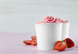Cups with tasty frozen yogurt and strawberries on pink wooden table. Space for text