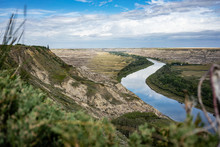 Reflective River Cutting Through The Alberta Badlands With Exposed Sedimentary Rock Canyon And Shrubs