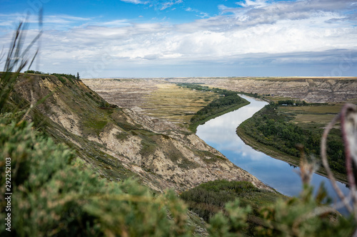 Reflective river cutting through the Alberta Badlands with exposed sedimentary r Canvas Print