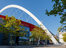 View Of Lanxess Arena, Indoor Multifunction Arena, With Glass Facade And Red Aluminium Cladding, And Long Span Roof Supported By White Steel Arch Beam And Cable In Cologne, Germany..