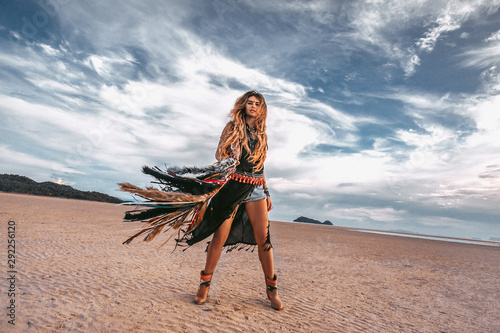 Fotomural young stylish hippie woman on the beach at sunset portrait