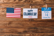 card with happy Columbus day inscription near American national flag and calendar paper sheet with 14 October date on wooden surface