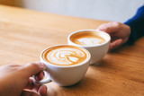 Close up image of a man and a woman clinking two coffee mugs on wooden table in cafe
