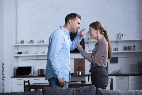 side view of angry husband and wife pointing with fingers and screaming at each other