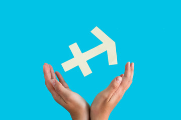 Sagittarius astrological sign hanging over female hands on blue background, horoscope forecast concept