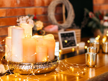 Romantic Home Decoration. Arrangement Of Fairy Lights And Candles Over Blur Brick Wall Background.