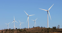 Alternative Energy Sources. Large Blades Of Wind Turbines In Rotation With The Blue Sky In The Background - Aerial View With A Drone - Environment & Ecological Concept