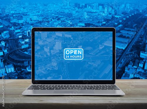 Open 24 hours flat icon with modern laptop computer on wooden table over city to Wallpaper Mural