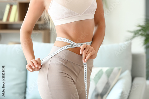 Fotografia Beautiful young woman with measuring tape at home
