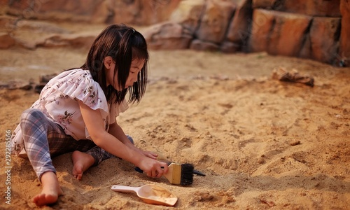 A young Asian girl playing in a sandbox with a modeled dinosaur fossil using brush and shovel Wallpaper Mural