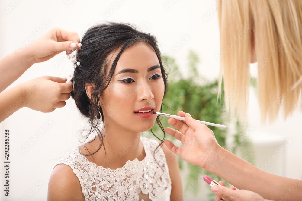 Fototapeta Professional makeup artist and hairdresser working with young Asian bride at home