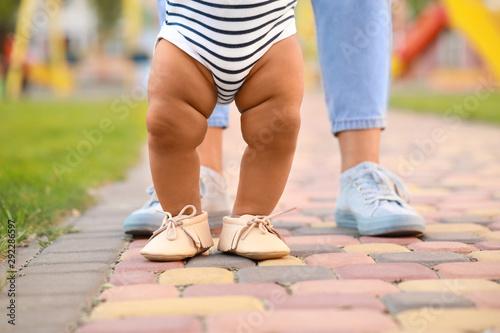 Obraz Cute little baby learning to walk outdoors - fototapety do salonu
