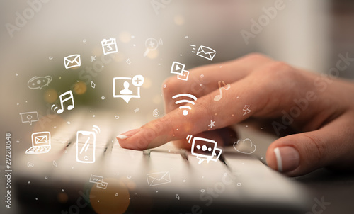 Business woman hand typing on keyboard with drawn application icons around - 292288548