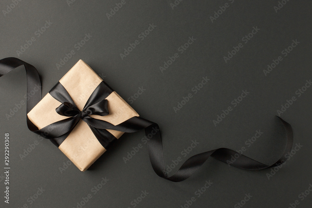Fototapety, obrazy: Craft gift box on a dark background, decorated with a textured bow and feathers, creating a romantic luxury atmosphere. For birthday, anniversary presents, gift post cards.