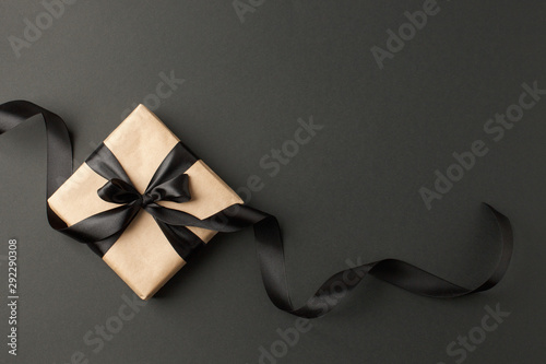 Photo  Craft gift box on a dark background, decorated with a textured bow and feathers, creating a romantic luxury atmosphere