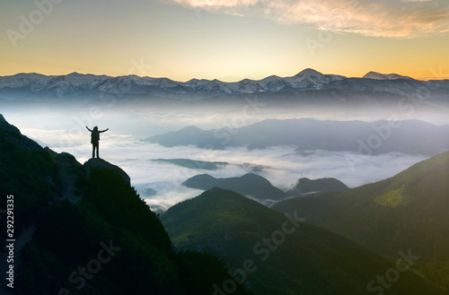 Foto auf AluDibond Schwarz Wide mountain panorama. Small silhouette of tourist with backpack on rocky mountain slope with raised hands over valley covered with white puffy clouds. Beauty of nature, tourism and traveling concept