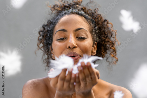 Valokuva African woman blowing feathers