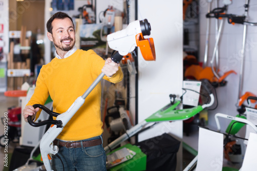 Smiling guy deciding on best manual lawnmower in garden equipment shop Tableau sur Toile