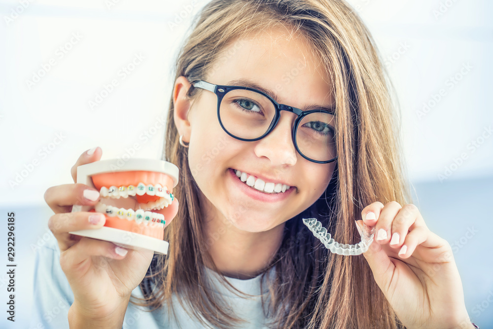 Fototapeta Dental invisible braces or silicone trainer in the hands of a young smiling girl. Orthodontic concept - Invisalign