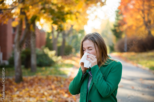 Canvastavla Sick young woman with cold and flu standing outdoors, sneezing, wiping nose with handkerchief, coughing