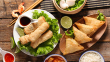 Selection Of Asian Food- Spring Roll, Samosa, Fried Noodles, Soup, Rice And Dumpling