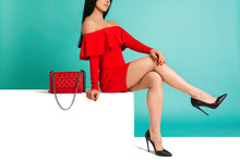 Beautiful Legs Woman Wearing Red Dress With Purse Hand Bag With High Heels Shoes Sitting On The White Bench
