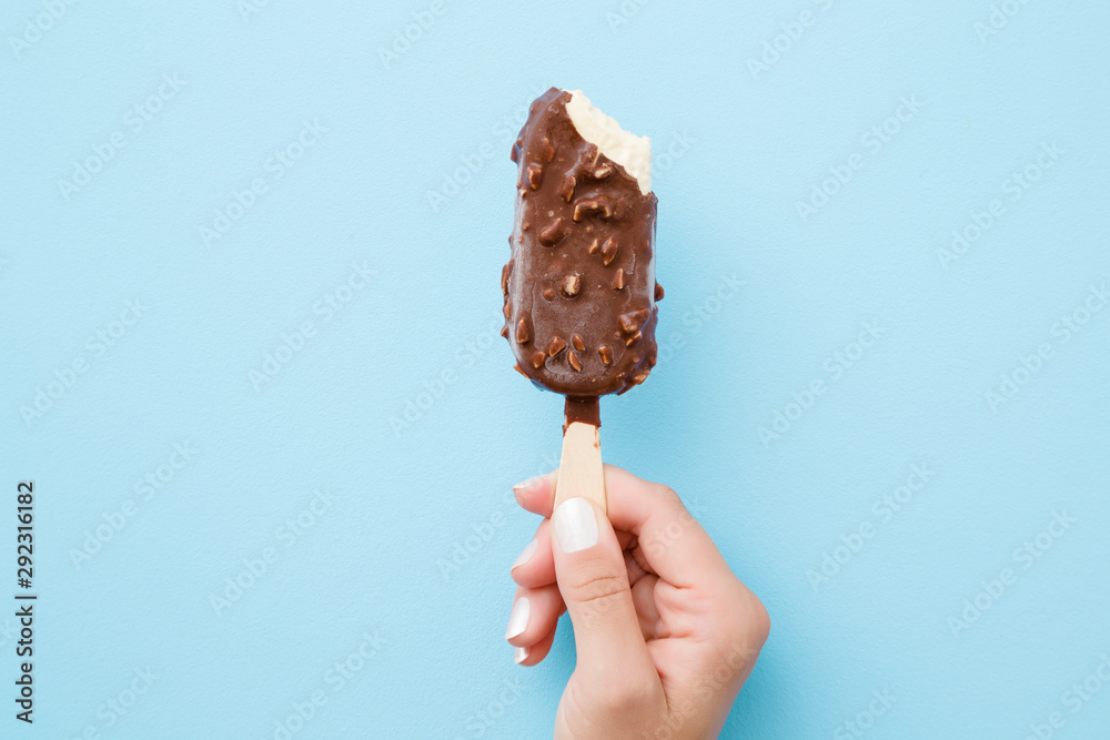 Fototapety, obrazy: Young woman hand holding white vanilla ice cream with nuts and chocolate glaze on pastel light blue background. Bitten food. Closeup.