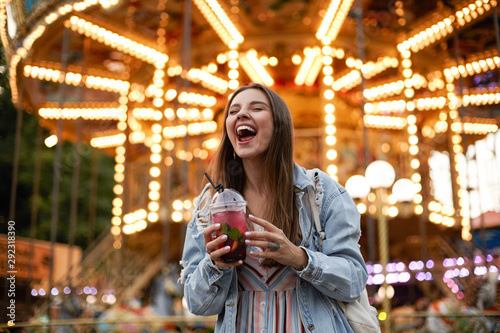 Staande foto Amusementspark Outdoor portrait of joyful young pretty brunette female in casual clothes posing over amusement park with closed eyes and broad smile, holding cup of lemonade in hands