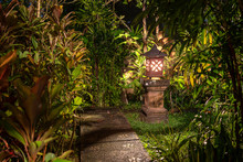 Decorative Lamp On The Stone Pillar Next To The Path In The Tropical Garden At Night . Island Bali, Indonesia . Nature Concept